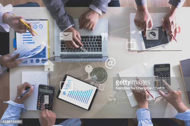 Digital Composite Of Icons Over Business People Working At Desk In Office