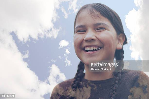Digital composite of laughing girl and clouds
