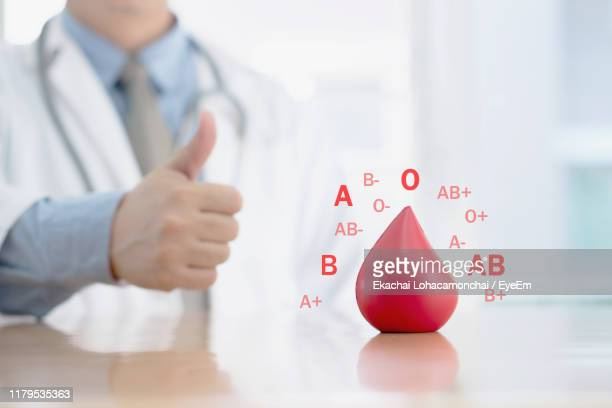 digital composite of male doctor with red blood drop and alphabets at desk - blood group stock pictures, royalty-free photos & images