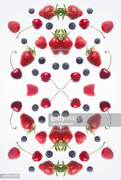 A digital composite of mirrored images of an arrangement of various berries and cherries