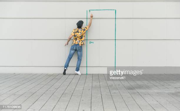digital composite of young man drawing a door at a wall - verandering stockfoto's en -beelden