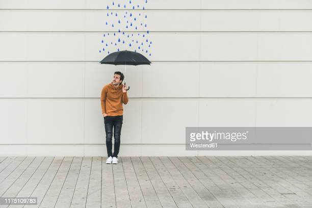 digital composite of young man holding an umbrella at a wall with raindrops - digital composite stock pictures, royalty-free photos & images