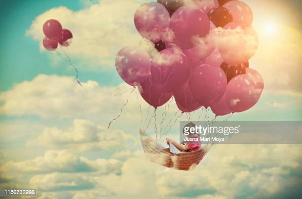 digital composition, of a boy flying on a paper boat fastened by pink balloons - imagination photos et images de collection