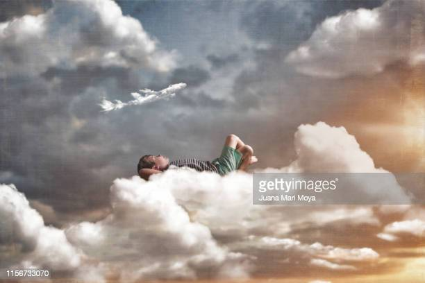 digital composition, of a child lying on a large cloud.  you are looking at a cloud shaped like an airplane. - dreamlike stock pictures, royalty-free photos & images