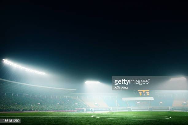 digital coposit of soccer field and night sky - stadio foto e immagini stock