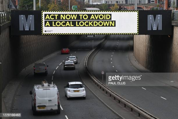 A digital display above a dual carriageway calls on residents to follow coronavirus guidlines in Manchester northwest England as the country battles...