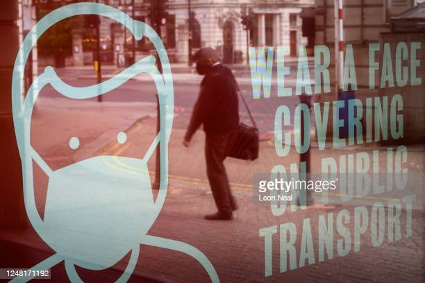 A digital display board in the entrance hall of Baker Street staition reminds travellers to wear a protective face mask when using public transport...