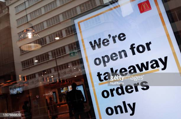 A digital display informs customers of takeaway service only in the window of a branch of fast food chain McDonald's on High Holborn in the...