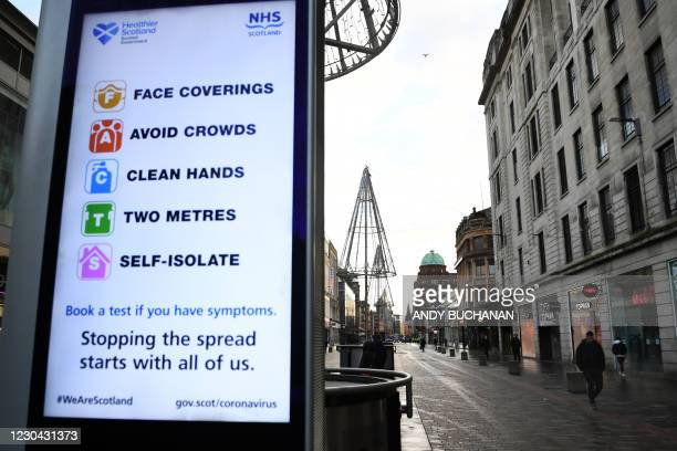 Digital display shows NHS Covid-19 guidance in Glasgow as Britain enters a national lockdown in London on January 5, 2021. - Prime Minister Boris...