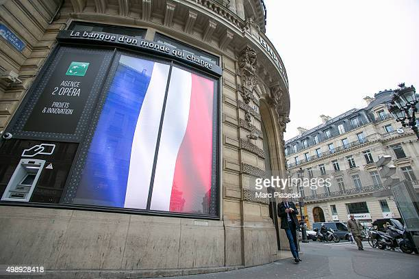 Digital french flags are seen on the 'BNP PARIBAS' bank building entrance on 'Place de l'Opera' in memory of the 130 victims of the Paris terrorist...