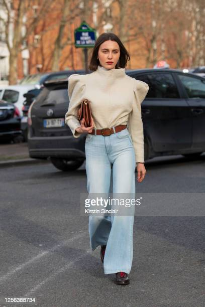 Digital influencer and model Mary Leest wears a Chloe bag, wide leg blue jeans, tan belt, brown shoes and a long sleeve cream top with butterfly...