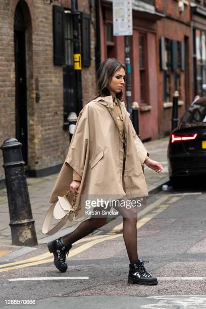 Digital Influencer and writer Isabella Charlotta Poppius wears a Maje jacket, belt and dress, Yuzefi bag and Ganni boots during London Fashion Week...
