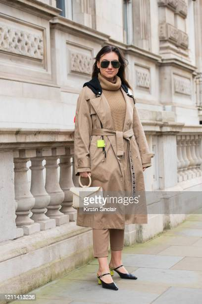 Digital influencer Andreea Cristea wears a Coach jumper Diesel coat HM trousers Complét bag Yuul Yie shoes and Carrera sunglasses during London...