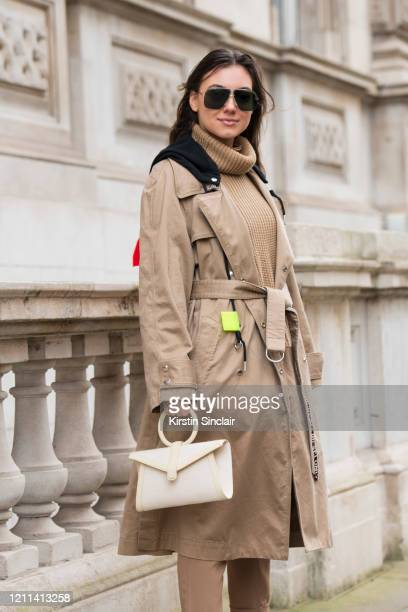 Digital influencer Andreea Cristea wears a Coach jumper Diesel coat HM trousers Complét bag and Carrera sunglasses during London Fashion Week...