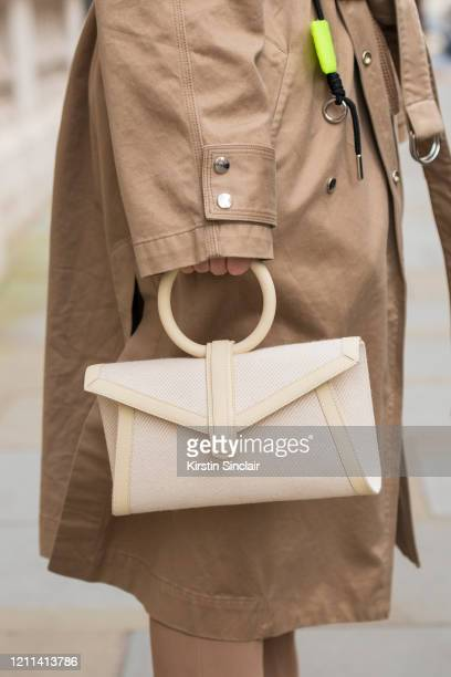 Digital influencer Andreea Cristea wears a Diesel coat and a Complét bag during London Fashion Week February 2020 on February 18 2020 in London...