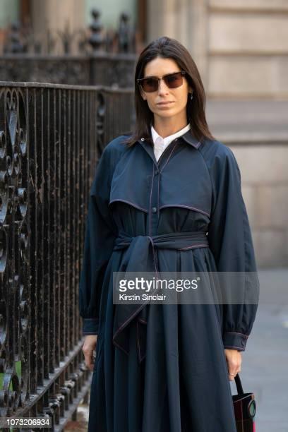 Digital influencer Deborah Reyner Sebag wears a navy trench coat during London Fashion Week September 2018 on September 17, 2018 in London, England.