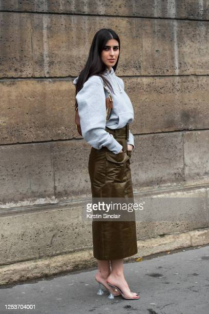 Digital Influencer Dima Al Sheikhly wears a Dior bag, Kristina Fidelskaya skirt, Amina Muaddi shoes and a Champion hooded jumper on March 02, 2020 in...