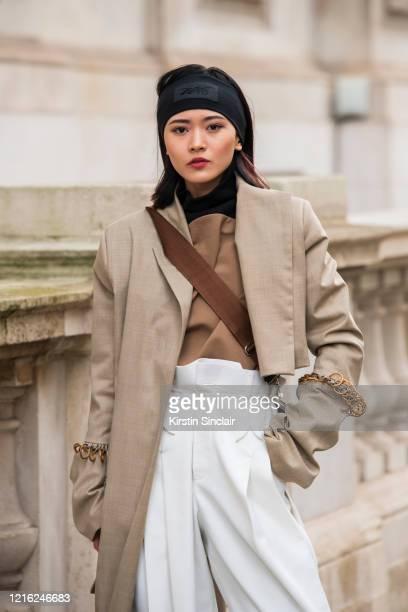 Digital Influencer Freya Sinyu Siu wears a Maison bent jacket Staff only top and trousers Victoria Beckham for Reebok headband during London Fashion...