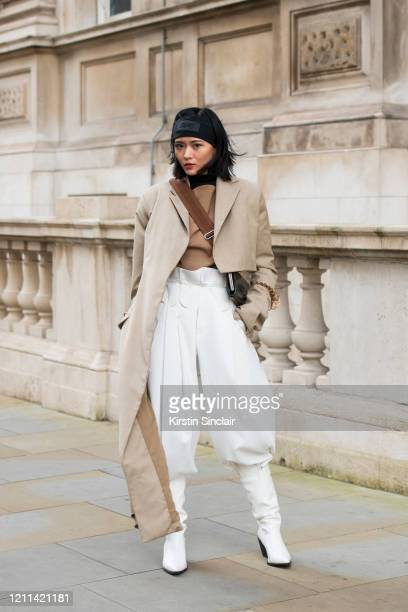 Digital Influencer Freya Sinyu Siu wears a Maison bent jacket vintage trousers Topshop boots during London Fashion Week February 2020 on February 18...