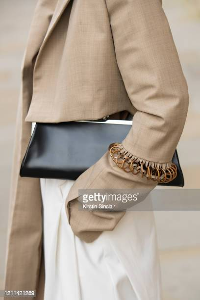 Digital Influencer Freya Sinyu Siu wears a Maison bent jacket vintage trousers and a black clutch bag during London Fashion Week February 2020 on...
