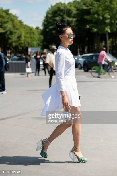 Digital influencer Jaime Xie wears a Jacquemus bag Alexander McQueen dress Charlotte Olympia shoes and Chanel sunglasses on July 02 2019 in Paris...