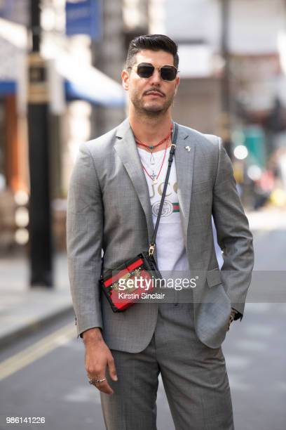 Digital influencer Kadu Dantas wears a Gucci T shirt Louis Vuitton bag Uniqlo sunglasses Brooks Brothers suit during London Fashion Week Men's on...