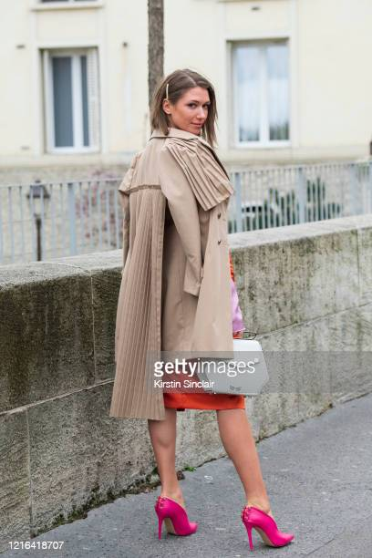Digital influencer Landiana Yolo wears a Maestoso bag, Hardot shoes, Ramelle skirt and a Chaotic trench coat on February 26, 2020 in Paris, France.