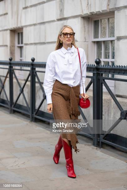Digital Influencer Leonie Hanne wears a Valentino shirt Balenciaga skirt Givenchy boots Anya Hindmarch bag and Karen Walker sunglasses during London...
