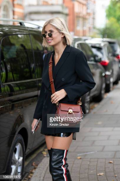Digital Influencer Xenia Adonts wears a Chloe bag Dior boots jacket shorts and hair clip during London Fashion Week September 2018 on September 16...