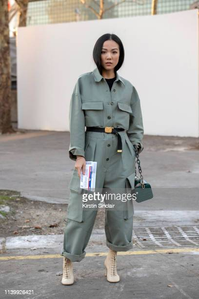 Digital Influencer Yoyo Cao wears Celine boots The Volon bag Frankie Shop boiler suit and Chanel belt and a on February 26 2019 in Paris France