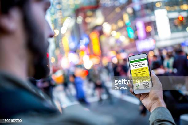 digital international certificate of covid-19 vaccination on smart phone - times square manhattan stock pictures, royalty-free photos & images