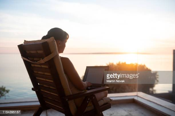a digital nomad enjoying sunset and working remotely - nomadic people stock pictures, royalty-free photos & images