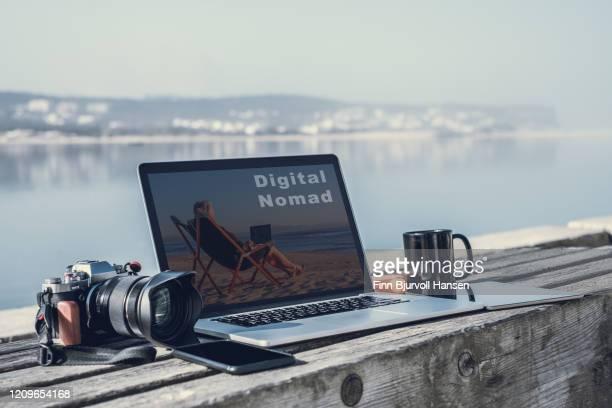 digital nomad - laptop and cameara on a bench, sea in the backround - finn bjurvoll - fotografias e filmes do acervo