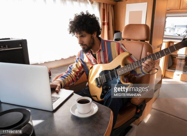 digital nomad young man guitar player in motorhome - nomadic people stock pictures, royalty-free photos & images