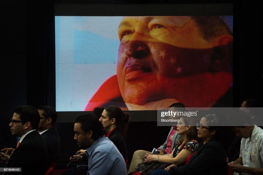 A digital screen displays an image of the late Venezuelan president Hugo Chavez as people attend the Petro cryptocurrency launch event in Caracas, Venezuela, on Tuesday, Feb. 20, 2018. Maduro launched Petro to use as a new alternative payment system amid hyperinflation and the eroding bolivar. Photographer: Wil Riera/Bloomberg via Getty Images