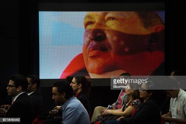 A digital screen displays an image of the late Venezuelan president Hugo Chavez as people attend the Petro cryptocurrency launch event in Caracas...