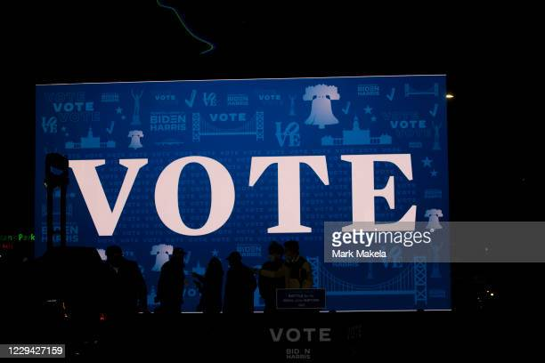 """Digital screen displays states """"VOTE"""" as campaign staff pose for photos on stage after Democratic vice presidential nominee Sen. Kamala Harris held a..."""