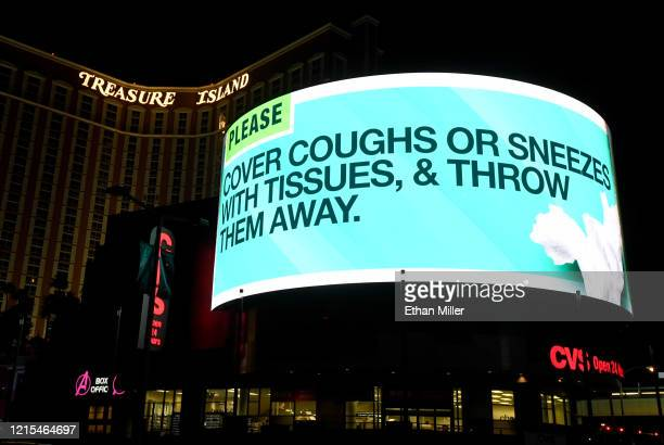 A digital sign above a CVS Pharmacy at the shuttered Treasure Island Hotel Casino on the Las Vegas Strip displays a message about coughing and...
