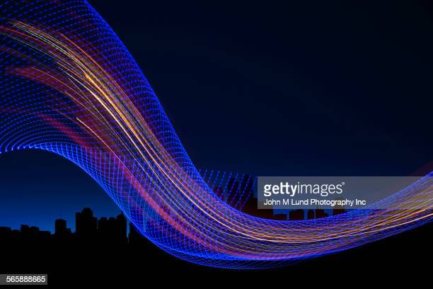 Digital stream on silhouette of city skyline at night