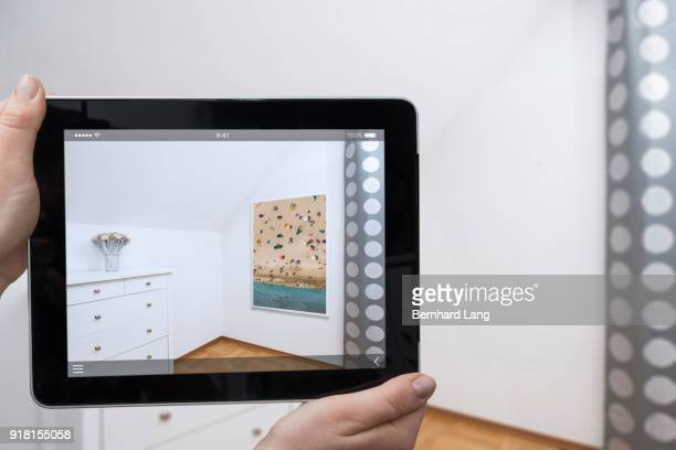 digital tablet displaying framed image in a room - realtà aumentata foto e immagini stock