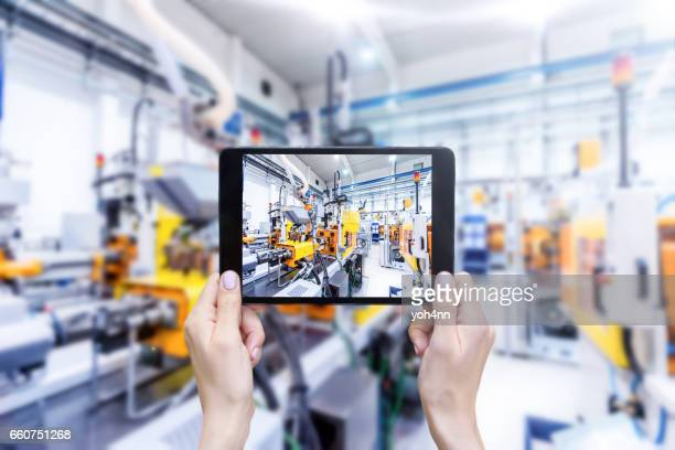 Digital tablet & futuristic industrial machinery