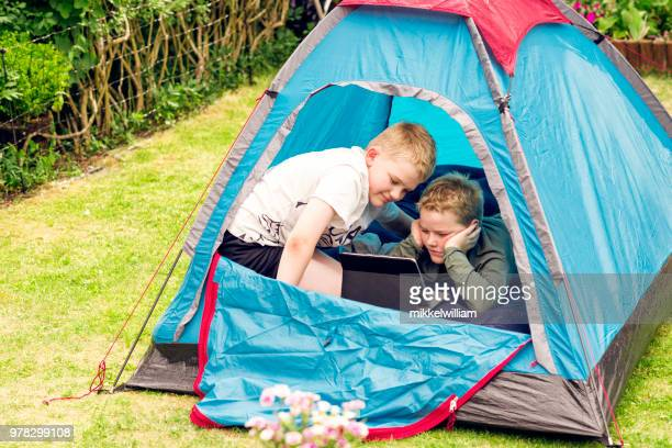 Digital tablet is used as entertainment tool for two boys on camping trip