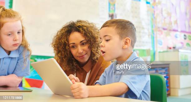 digital tablet learning - primary age child stock pictures, royalty-free photos & images