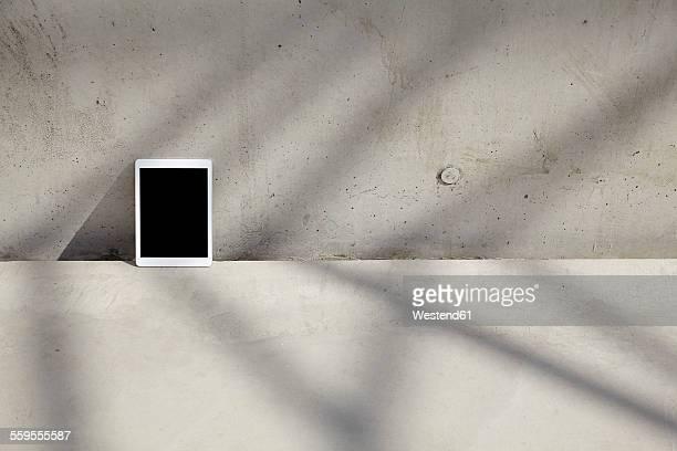 Digital tablet on concrete floor