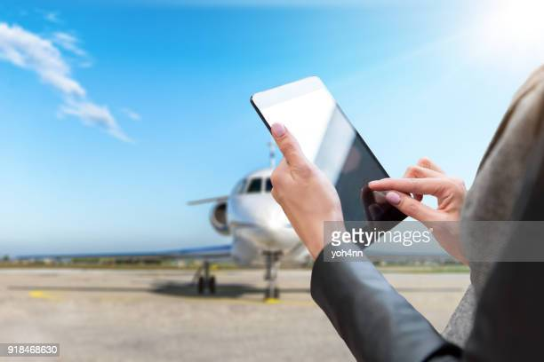 digital tablet & private jet - making a reservation stock photos and pictures