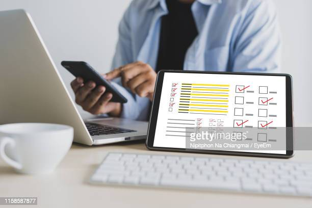 digital tablet showing various icons against person working in office - school icon stock photos and pictures