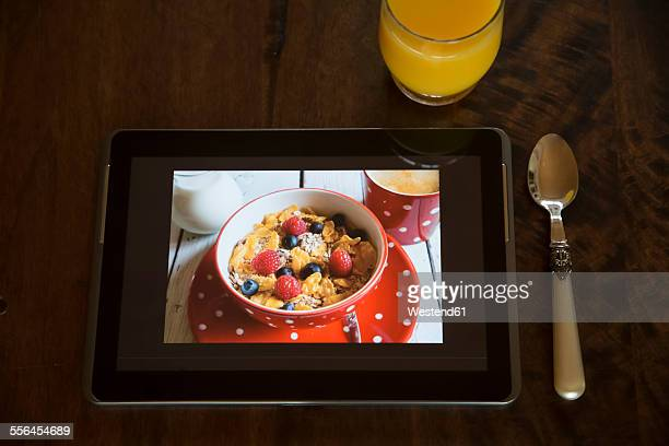Digital tablet with photography of granola, glass of juice and spoon on wood