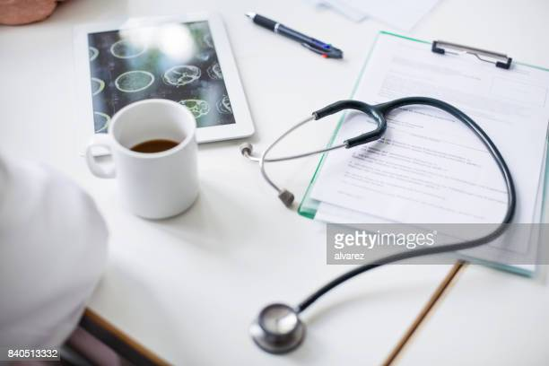 Digital tablet with stethoscope and medical report on table.