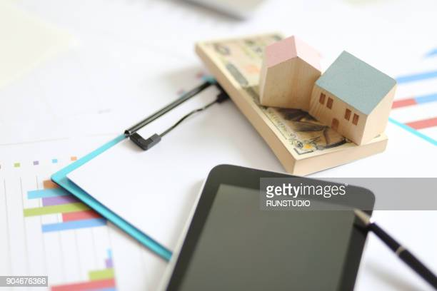 digital tablet,model house, paper moneys and paperwork on table - japanese yen note stock photos and pictures