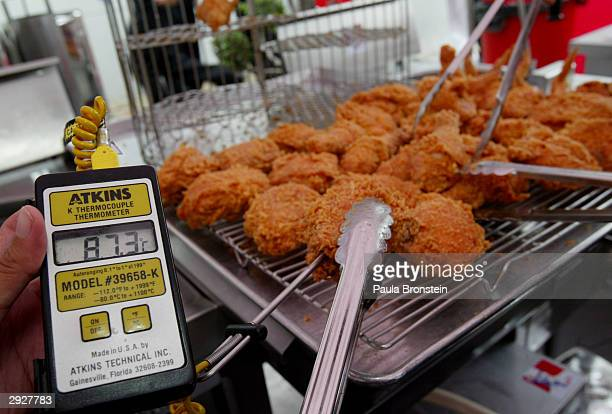 Digital thermometer is used to test the temperature of the chicken before it is served as Kentucky Fried Chicken is served at a free chicken lunch...